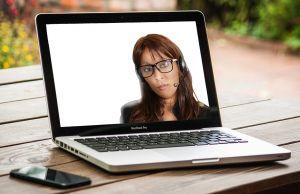 Een laptop waarop je een vrouw ziet videobellen.