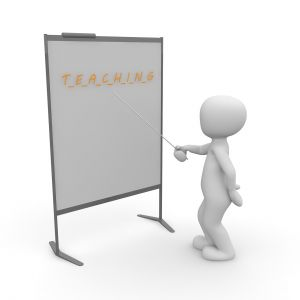 Figuurtje staat voor een bord met het opschrift teaching