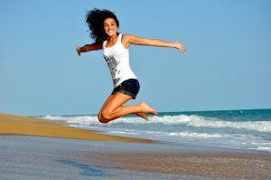Springende vrouw op het strand