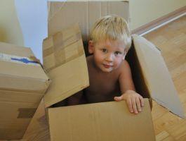 Kleuter speelt met een kartonnen doos