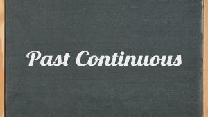 Krijtbord met de woorden past continuous erop geschreven