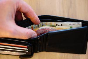 Hand neemt geld uit portemonnee