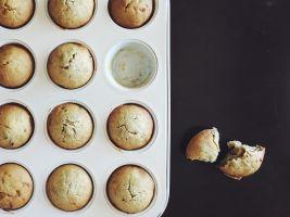 Een bakplaat voor cupcakes, gevuld met gebakken cupcakes. Er werd al van een cakeje geproefd.