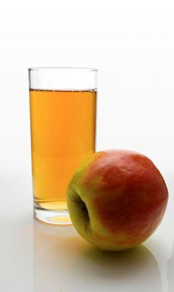 Een glas met appelsap, er ligt een rode appel naast het glas.