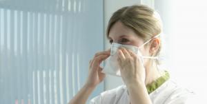 Verpleegster zet een mondmasker op