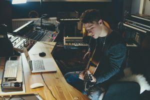 Een jongen speelt gitaar aan de laptop en componeert muziek.