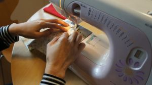 Two hands putting pieces of fabric together with the sewing machine.
