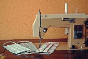 A sewing machine, on the foot are 3 mouth masks.