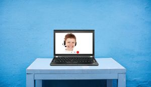 Een laptop op een tafel. Op het scherm zie je dat er een webinar bezig is.