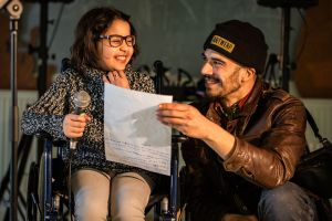 Een man en een meisje kijken lachend naar de tekst op een blad.