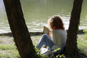 vrouw leunt tegen een boom en leest een boek