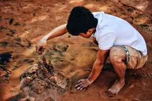 Een jongen maakt een kasteel van modder en zand.