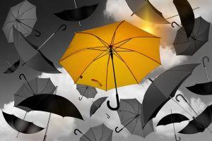 Verschillende paraplu's in de lucht. Eén paraplu is geel. Het symboliseert verdriet en vreugde