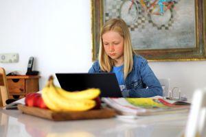 Meisje achter laptop aan een tafel in de woonkamer