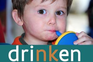 jongen drinkt uit een beker met rietje
