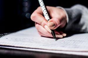 Een hand houdt een balpen vast. De eerste regels zijn reeds geschreven op het papier.