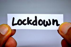 handen houden papiertje vast waarop lockdown staat