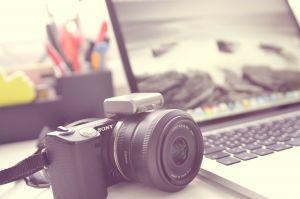 Fotocamera naast een laptop