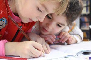 2 kinderen tekenen in een schriftje