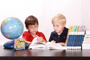 twee kinderen kijken samen in een boek