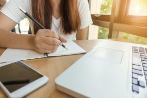 leerlinge aan laptop met smartphone, balpen en schriftje