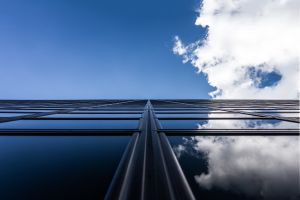 Een weerspiegeling van lucht en wolken in een glazen gebouw.