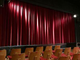 een rij stoelen voor een podium waarop het rode doek nog gesloten is