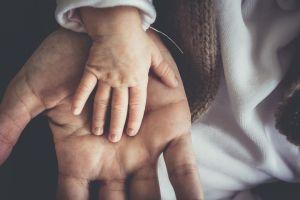 kinderhandje in een grotere hand