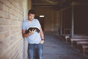 Young man leans a book against a wall