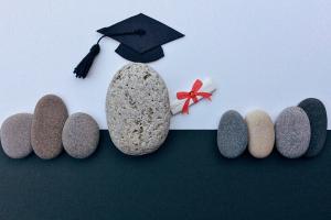 Leerlingen en leraar voorgesteld door keien. De leraar deelt het diploma uit.