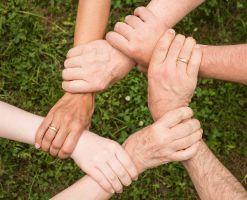 zes handen die elkaar vastnemen