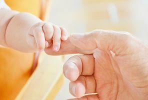 iemand die een babyhandje vastneemt