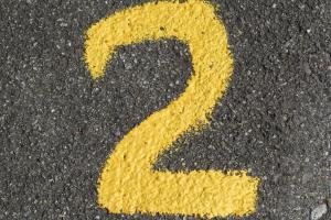 cijfer 2 met gele verf op de grond geschilderd