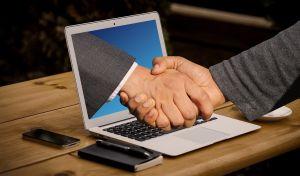 Er worden handen geschud, bij wijze van akkoord. Eén hand komt uit het scherm van een laptop.