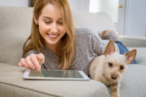Girl works on tablet. She's holding a dog.