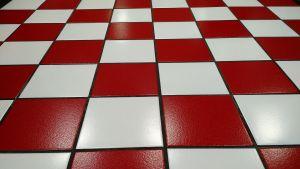 Een vloer met rode gekleurde vierkanten. Een dambord patroon.