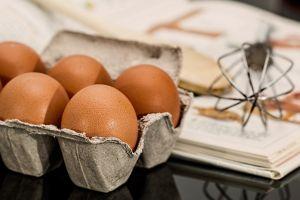 eieren, een garde en een opengeslagen kookboek