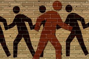 mannetjes geschilderd op de muur, één mannetje loopt naar de andere richting