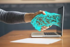 Een computer hand lijkt uit het scherm van de laptop te komen. Hij schudt de hand van de laptopgebruiker.