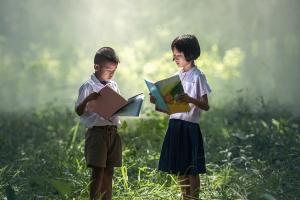 twee kinderen lezen in een bos