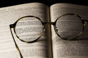 bril ligt op een opengeslagen boek