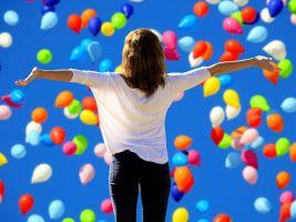 iemand met open armen voor een hoop ballonnen