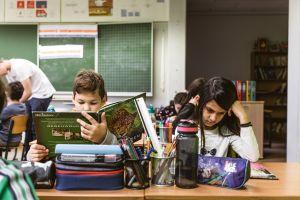 twee leerlingen zitten aan de schoolbank en lezen