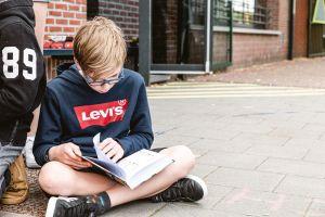jongen zit op de speelplaats in kleermakerszit te lezen met een boek op zijn schoot