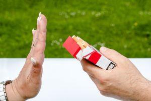 iemand steekt hand op naar een pakje sigaretten