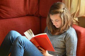 meisje leest een boek in een rode zetel