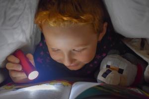kind leest met een zaklamp in bed