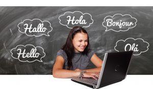 leerling aan computer voor krijtbord met 'hallo' in verschillende talen