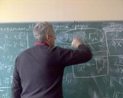 leraar schrijft wiskundige bewerkingen op schoolbord