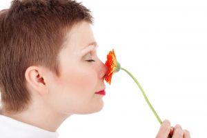een vrouw ruikt aan een bloem